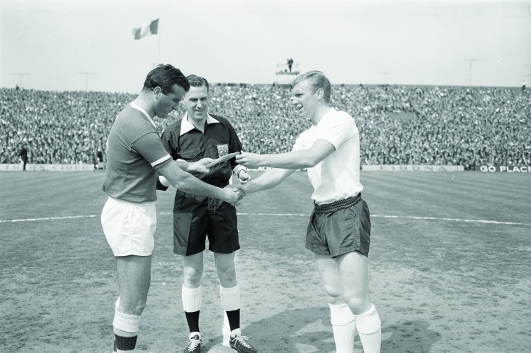 24/05/1964 05/24/1964 24 May 1964 Soccer International: Ireland v England at Dalymount Park, Dublin. England won the game 3-1.  Irish captain, Noel Cantwell (left) and English captain Bobby Moore shake hands and exchange plaques prior to the match with referee Robert Holley Davidson (Scotland) looking on.